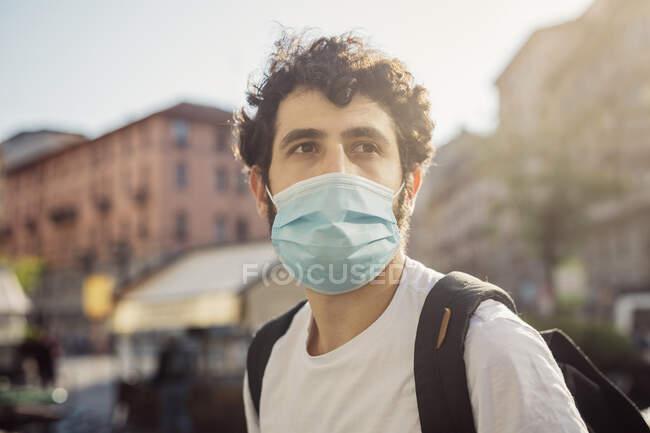Close-up de jovem pensativo usando máscara facial olhando para longe na cidade — Fotografia de Stock