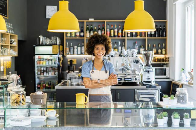 Щаслива жінка - бариста, що стоїть у кафе. — стокове фото