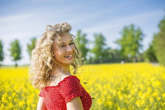 Sorridente donna matura indossa abito rosso in piedi contro semi oleosi stupri — Foto stock