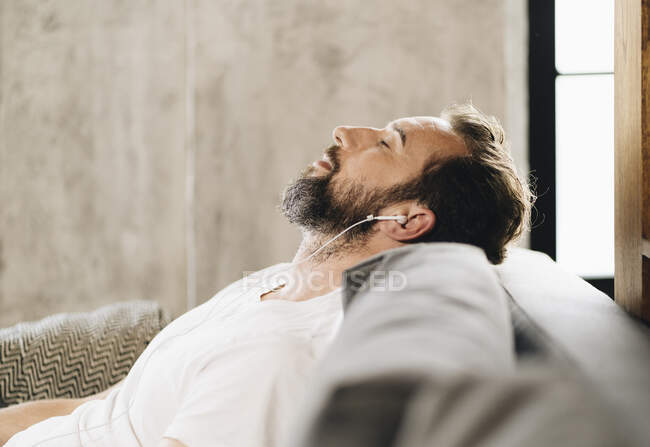 Homem maduro sentado no sofá, relaxante, ouvindo música com fones de ouvido — Fotografia de Stock
