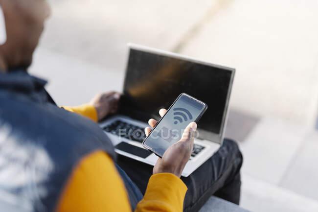 Gros plan d'un homme utilisant un ordinateur portable et un smartphone pour faire du shopping en ligne — Photo de stock