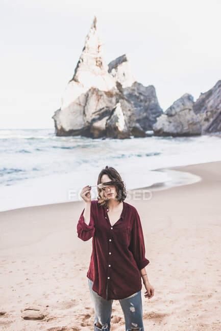 Jeune femme couvrant les yeux de plumes alors qu'elle se tenait debout à la plage d'Ursa, région de Lisboa, Portugal — Photo de stock