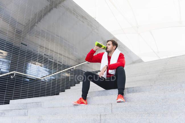 Молодой человек отдыхает от тренировки, пьет из бутылки. — стоковое фото