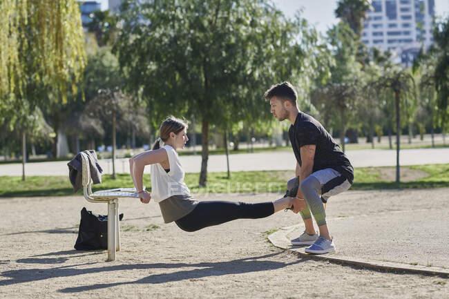 Mujer durante el entrenamiento con el entrenador en el parque - foto de stock