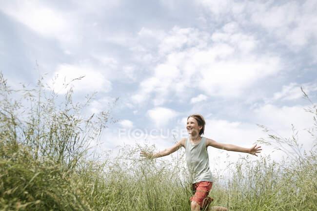 Porträt eines glücklichen Jungen, der mit ausgestreckten Armen auf einem Feld läuft — Stockfoto