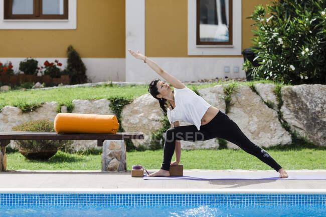 Зрелая женщина практикует треугольное положение у бассейна напротив дома во дворе — стоковое фото