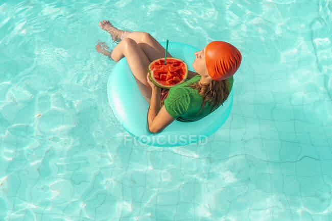Mujer con neumático flotante y sandía relajante en piscina - foto de stock