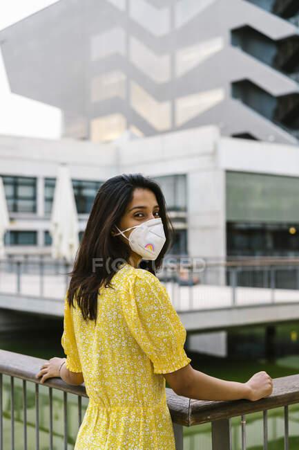Молода жінка в масці, стоячи на підвищеному проході в місті. — стокове фото