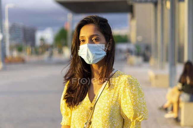 Mujer joven con máscara facial mientras está de pie en la calle de la ciudad - foto de stock