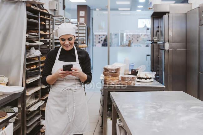 Щаслива жінка-пекар використовує смарт-телефон у пекарні. — стокове фото
