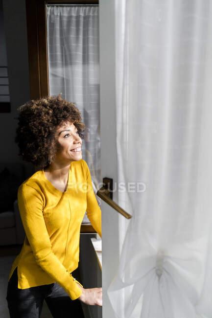 Retrato de la joven feliz de pie en la ventana abierta mirando hacia arriba - foto de stock