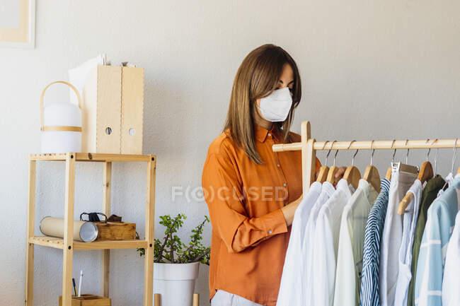 Designer de moda feminina trabalhando em casa com roupas stand usando máscara protetora — Fotografia de Stock
