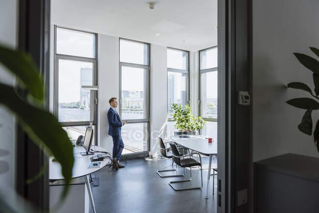 Homme d'affaires debout à la fenêtre thw dans le bureau — Photo de stock