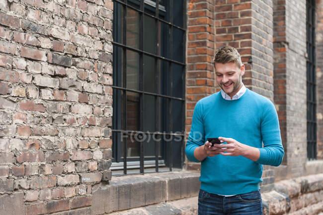 Sorridente giovane uomo d'affari utilizzando smartphone in un edificio di mattoni — Foto stock