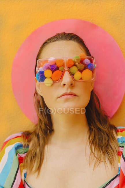 Retrato de mujer con gafas con pompones de colores que cubren sus ojos - foto de stock