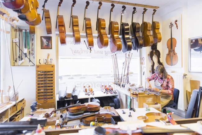 Жіночий скрипковий майстер на роботі в майстерні. — стокове фото