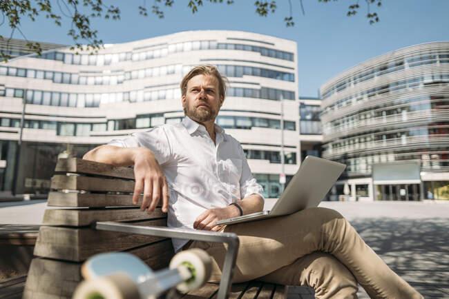 Бізнесмен сидить на лавці в місті за допомогою ноутбука. — стокове фото