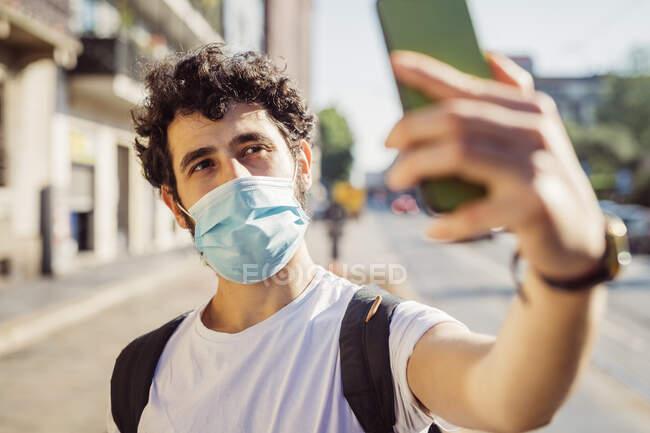 Primer plano del hombre con máscara facial tomando selfie con teléfono inteligente en la ciudad - foto de stock