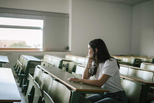 Jeune femme réfléchie regardant ailleurs tout en étant assis au bureau — Photo de stock