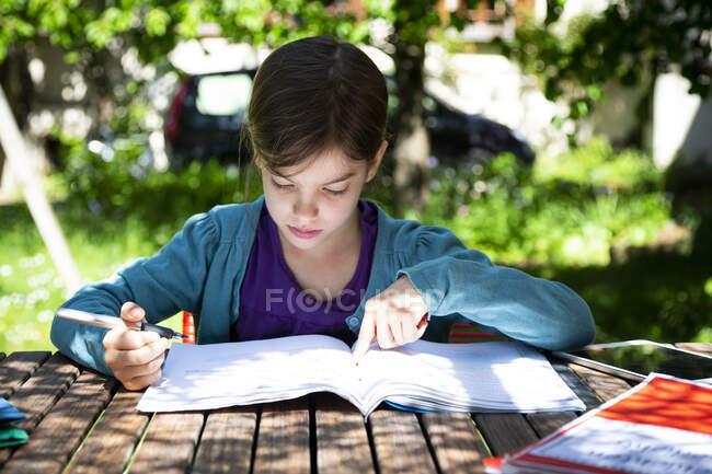 Girl sitting at garden table doing homework — Stock Photo
