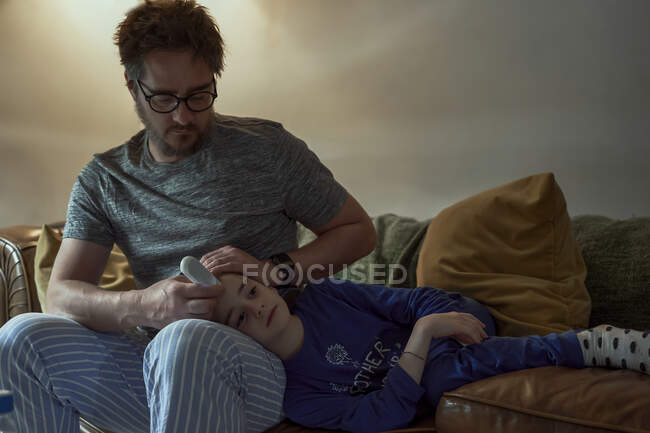 Hombre sosteniendo termómetro en la frente de la hija enferma en la sala de estar en casa - foto de stock