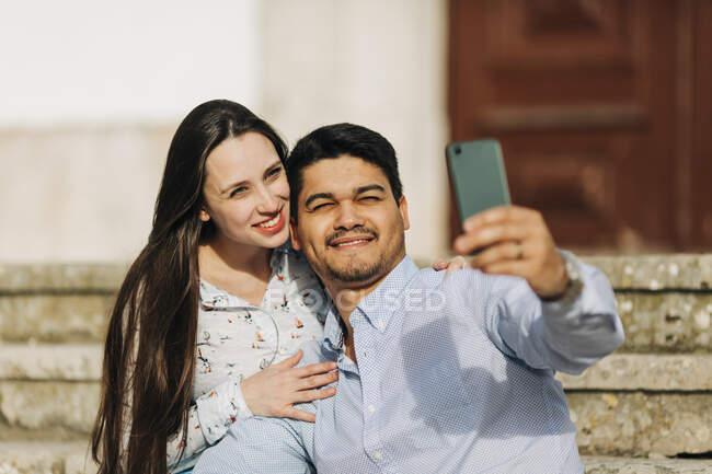 Счастливая будущая пара делает селфи через смартфон в солнечный день — стоковое фото