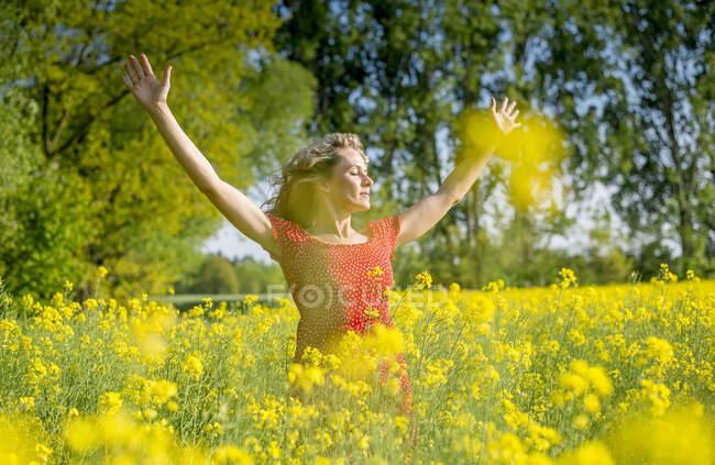 Donna vestita di rosso con le braccia alzate in piedi tra colza e semi oleosi — Foto stock