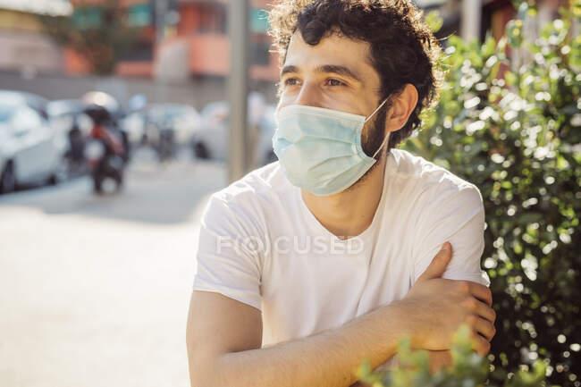 Close-up de jovem pensativo usando máscara facial enquanto sentado no café da calçada — Fotografia de Stock