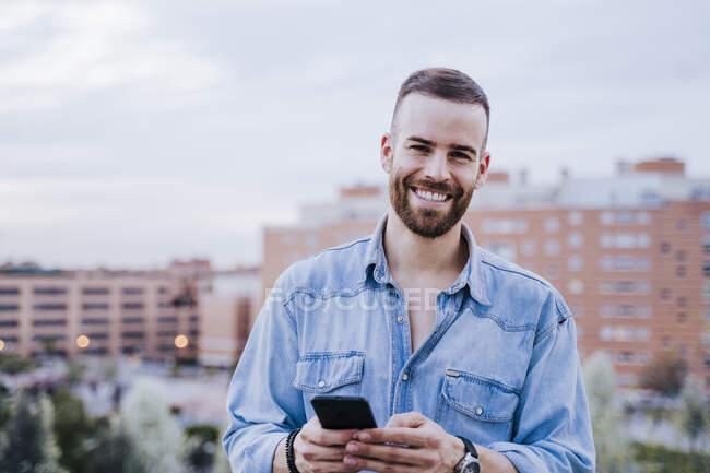 Ritratto di giovane rilassato con smartphone all'aperto — Foto stock