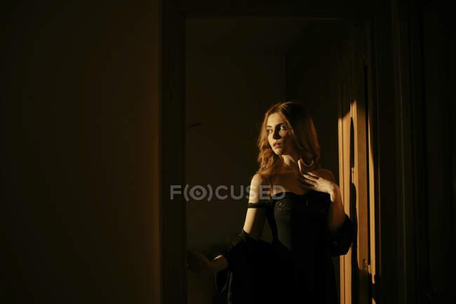 Mulher loira bonita em lingerie preta em casa — Fotografia de Stock