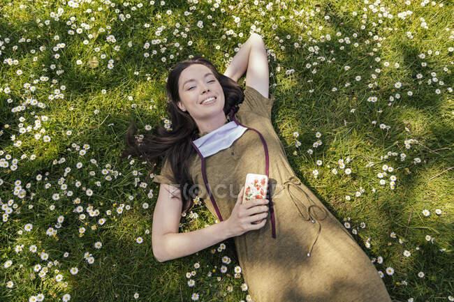 Mulher com máscara facial decepcionada desfrutando de seu tempo livre enquanto deitada na grama com margaridas — Fotografia de Stock
