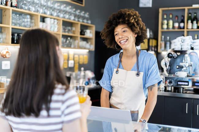 Щаслива господиня розмовляла з молодою жінкою за прилавком у кафе. — стокове фото