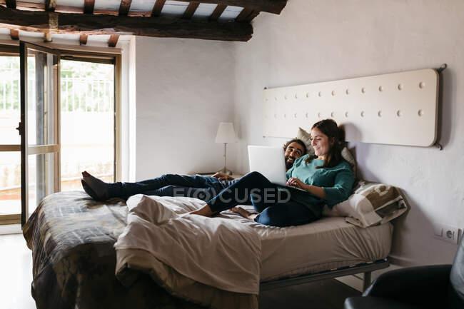 Pärchen schaut Film sitzend auf Bett zu Hause — Stockfoto