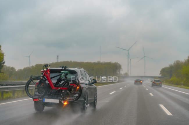 Motorway during rain, car with bike rack — Stock Photo