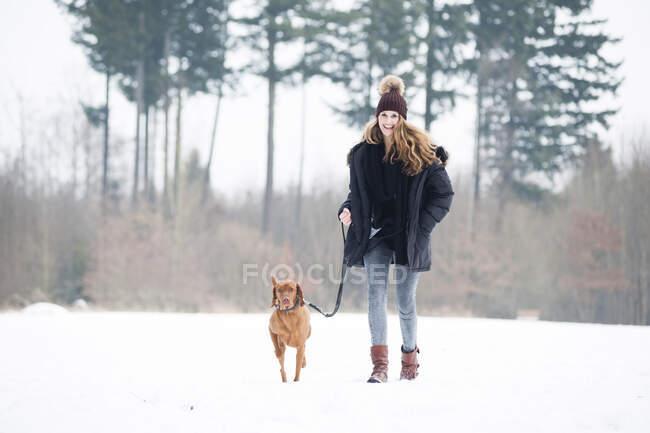 Mujer joven sonriente paseando con el perro en la nieve contra los árboles en el bosque - foto de stock