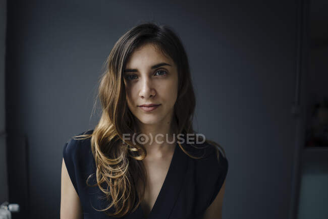 Portrait of serious young woman against grey background — Stock Photo