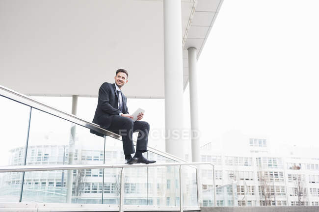 Businessman holding digital tablet while sitting on glass railing — Stock Photo