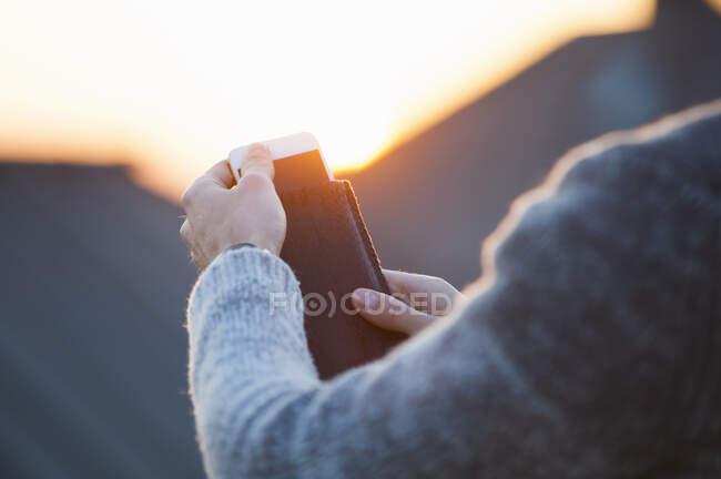 Imagen recortada de la mujer que quita el teléfono inteligente de la cubierta durante la puesta del sol - foto de stock
