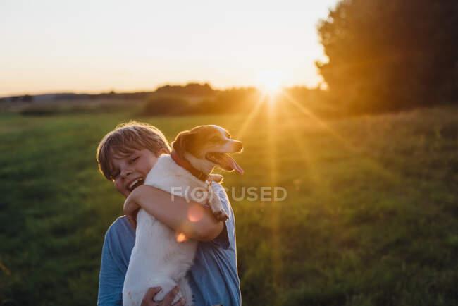 Niño juguetón con perro en el campo durante el atardecer, Polonia - foto de stock