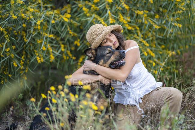 Mujer joven usando sombrero mientras abraza perro en plantas, Alicante, provincia de Alicante, España - foto de stock