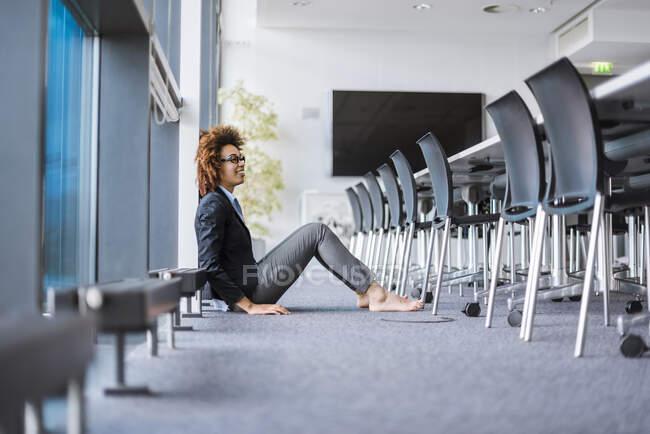 Усміхнена молода бізнесменка сидить на підлозі в конференц-залі. — стокове фото