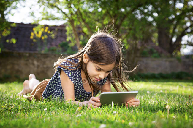 Smiling girl lying on meadow in the garden using digital tablet — Stock Photo
