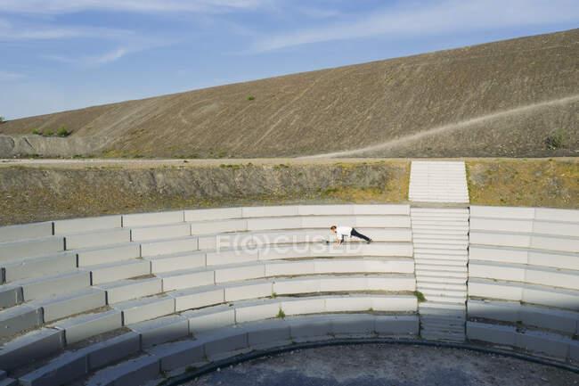 Empresario masculino maduro haciendo ejercicio en el anfiteatro BergArena pasos en un día soleado - foto de stock