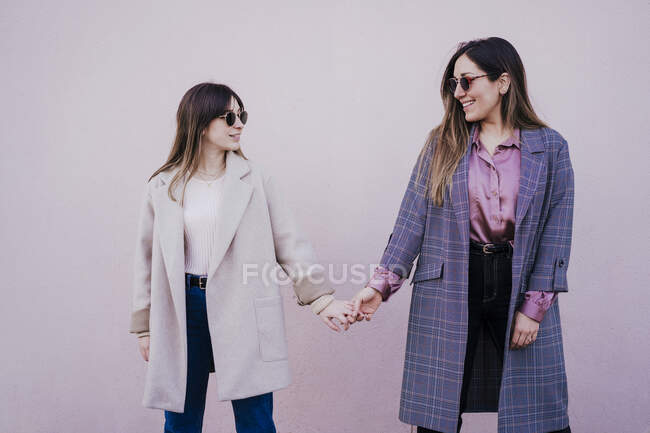 Two fashionable friends holding hands — Stock Photo