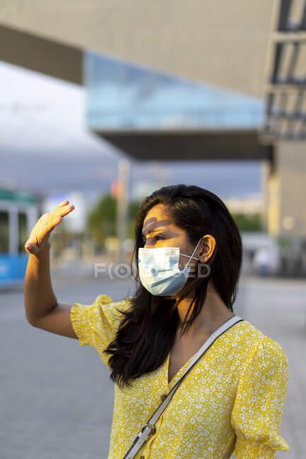 Mujer joven con máscara que protege los ojos mientras está de pie en la calle de la ciudad - foto de stock