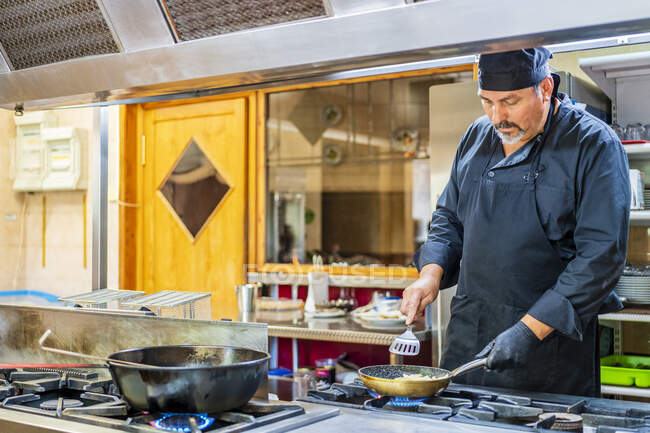 Chef with pan in traditional Spanish restaurant kitchen — Stock Photo