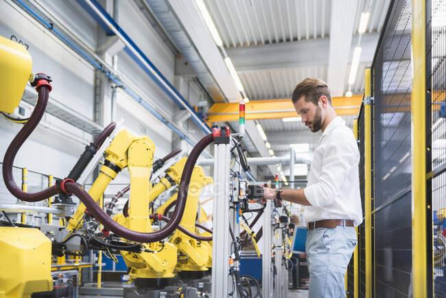 Visão lateral de robótica confiante especialista examinando máquinas na fábrica — Fotografia de Stock