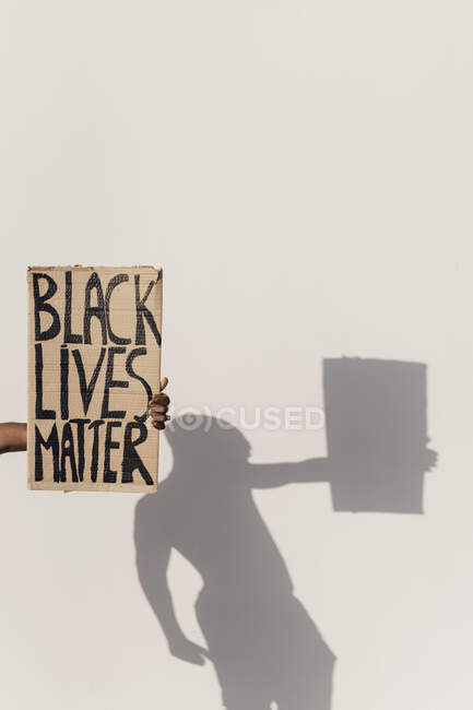 Рука тримає знак Чорного Життя, тінь людини на стіні — стокове фото