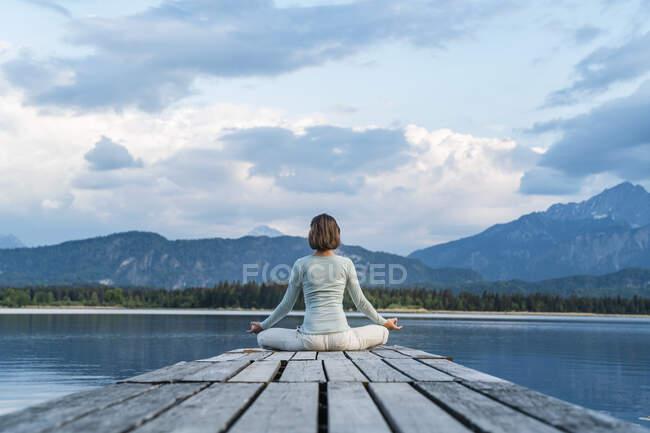 Взрослая женщина медитирует, сидя на причале над озером на фоне облачного неба — стоковое фото
