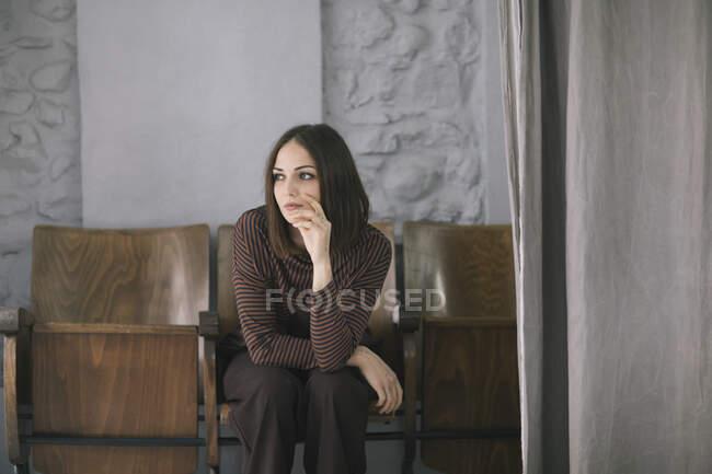 Jeune femme réfléchie assise sur une chaise dans un studio de conception de vêtements — Photo de stock